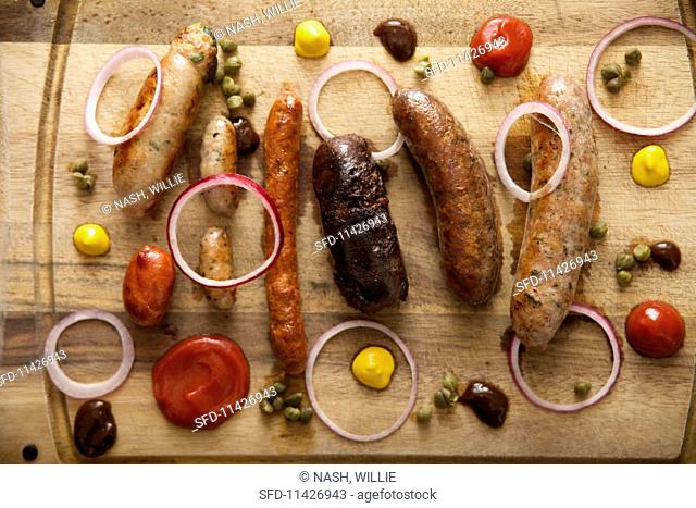 A wooden platter with various sausages and spices