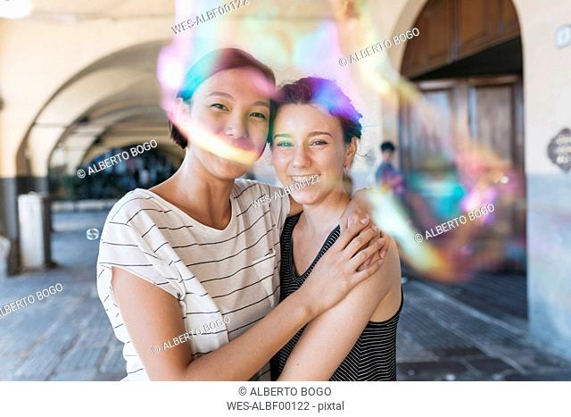 Two young women playing with soap bubbles