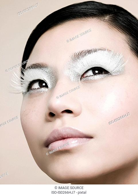 A young woman wearing white false eyelashes