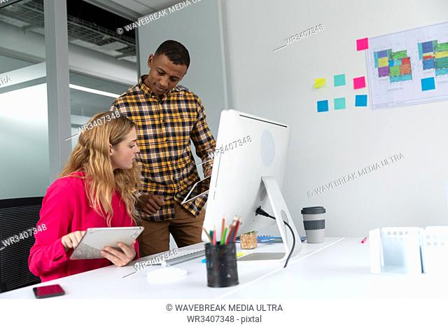 Side view of a young African American man standing and a young Caucasian woman sitting at a desk using tablet computers in the modern office of a creative...