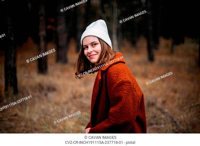 Close-up portrait of pretty young lady standing in forest