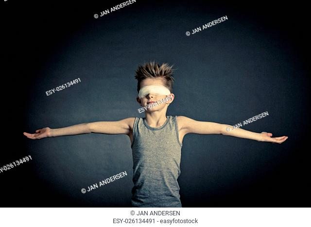 Conceptual Slim Young Boy with Covered Eyes Raising his Arms on Sideways Against Gray Gradient Background