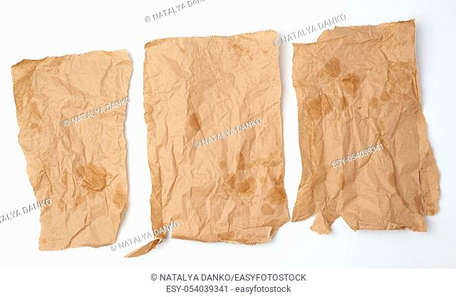 three torn crumpled pieces of brown paper with grease stains on a white background, top view