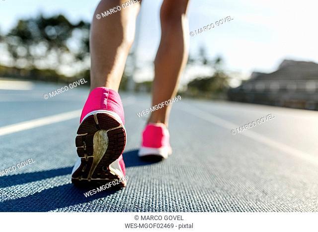 Legs of female athlete running on racetrack