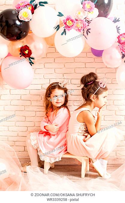 Two beautiful little girls with crowns under birthday balloon and paper flower arch decorations. Childish photozone for celebration