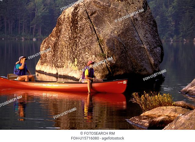 Vermont, canoe, canoeing, Mother and daughter sitting together in canoe on Kettle Pond next to a huge boulder in Groton State Forest