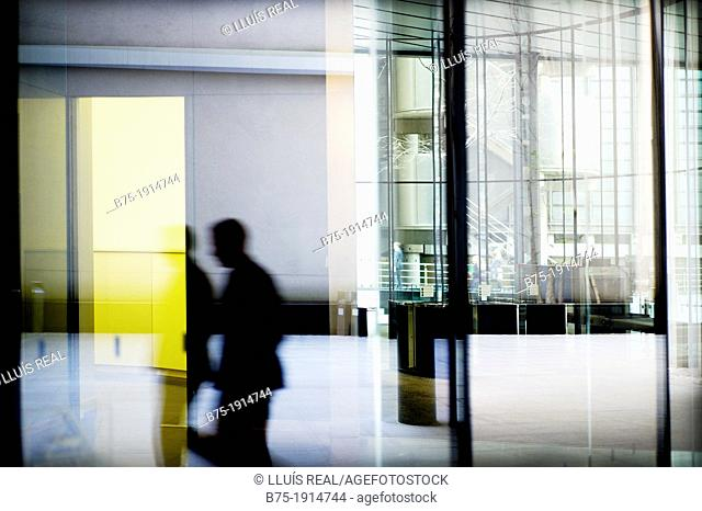reflection of an executive walking down the hall of an office building in City of London, England, UK