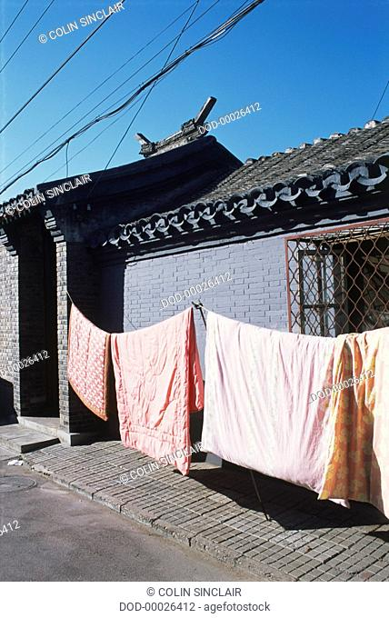 China, Beijing, blankets hanging on a washing line outside a hutong house