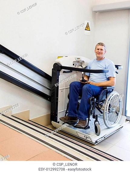 man in an invalid chair walks upstairs on the special elevating device