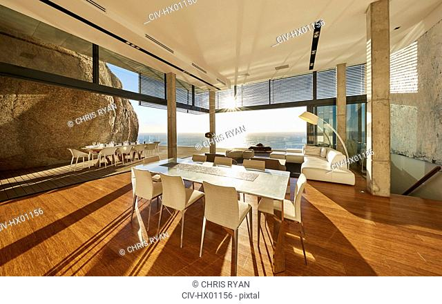Sun shining in modern luxury home showcase dining room with ocean view