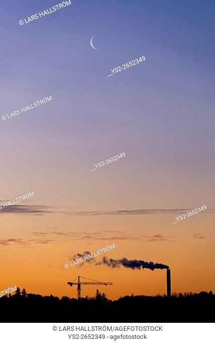 Industry silhouette, smokestack and construction crane with copy space on night sky. Concept of urban development and environment
