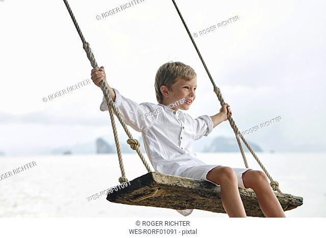 Thailand, Ko Yao Noi, happy boy on a swing on the beach