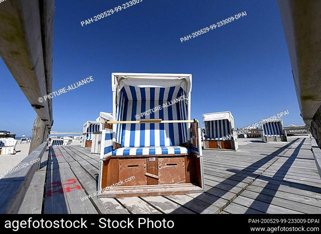 29 May 2020, Schleswig-Holstein, St.Peter-Ording: Beach chairs can be found at the North Sea beach with blue sky. For the North Frisian islands and Halligen of...