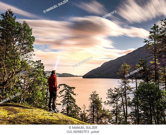 Male hiker looking up at evening stars, Comox Lake, Courtenay, Vancouver Island, British Columbia, Canada