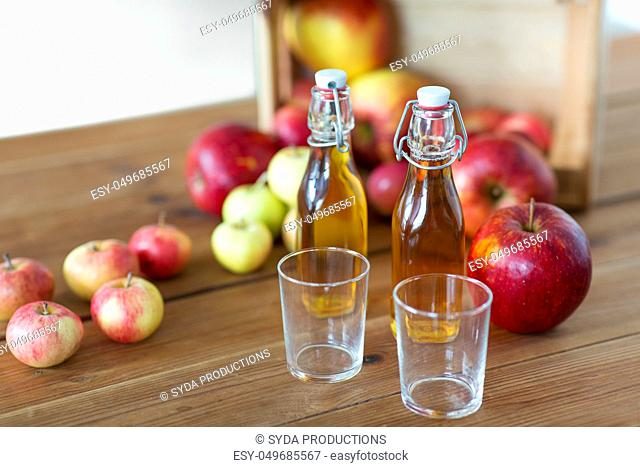 glasses and bottles of apple juice on wooden table