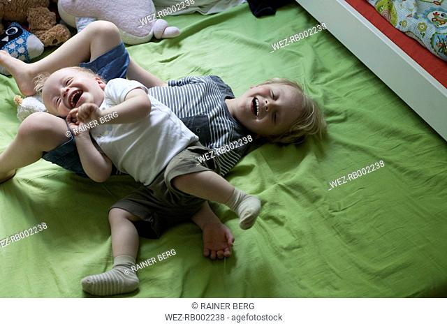 Two little brothers rampaging on bed