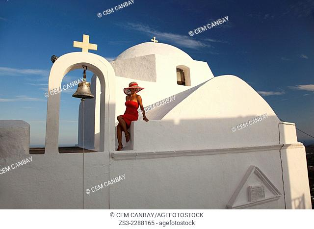 Woman looking down from the stairs of a church in Hora, Serifos, Cyclades Islands, Greek Islands, Greece, Europe
