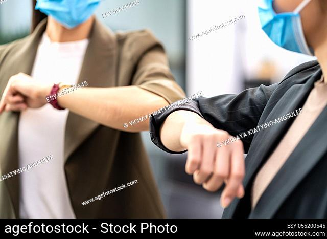Close up two businesswomen do alternative greeting in new normal office lifestyle. They wear protective face mask and use elbow bump instead of handshake to...