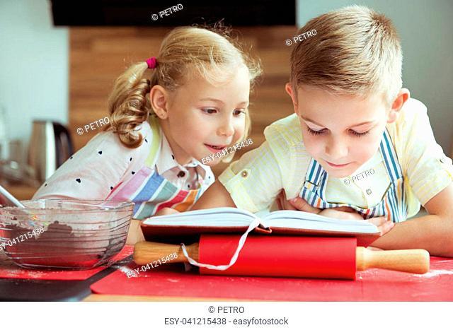 Two beautiful and happy children having fun exploring recept before preparing christmas cookies
