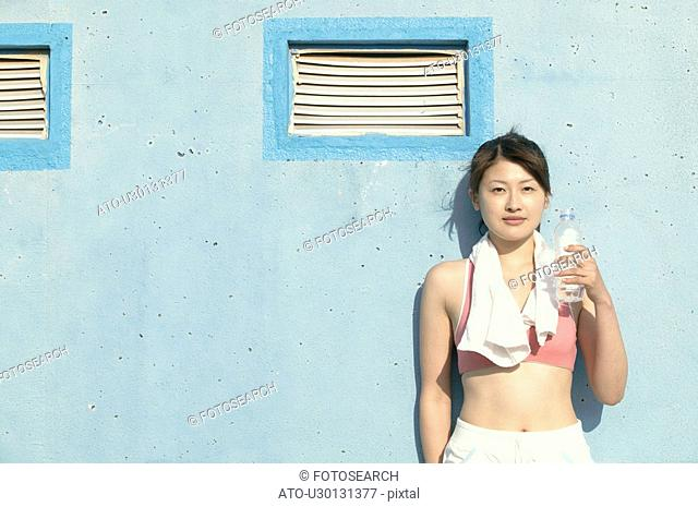 A young woman holds the bottle of water as she stares at the camera