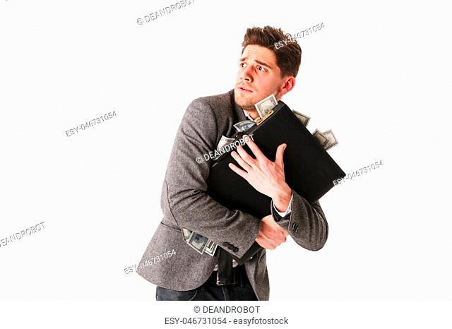 Portrait of a scared young businessman holding briefcase full of money isolated over white background