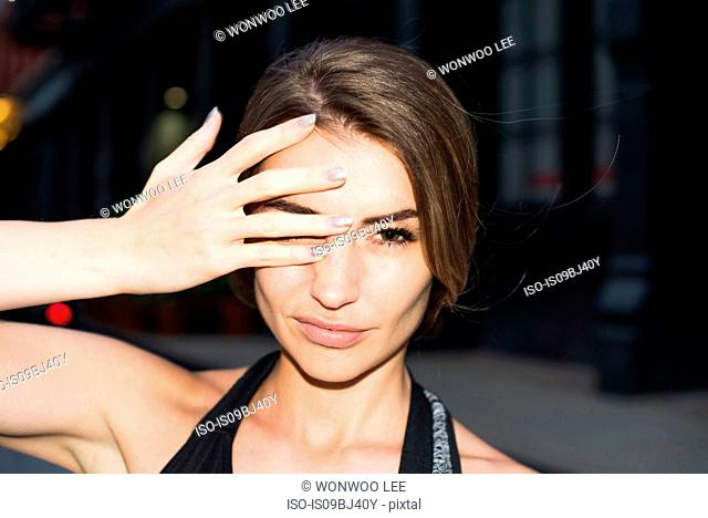 Portrait of woman, hand covering eye looking at camera, New York, USA