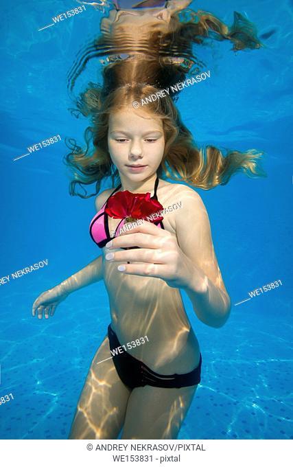 Beautiful teen girl posing under water in the pool