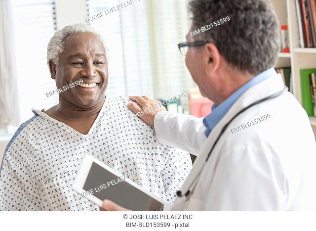 Doctor with digital tablet comforting older man in hospital