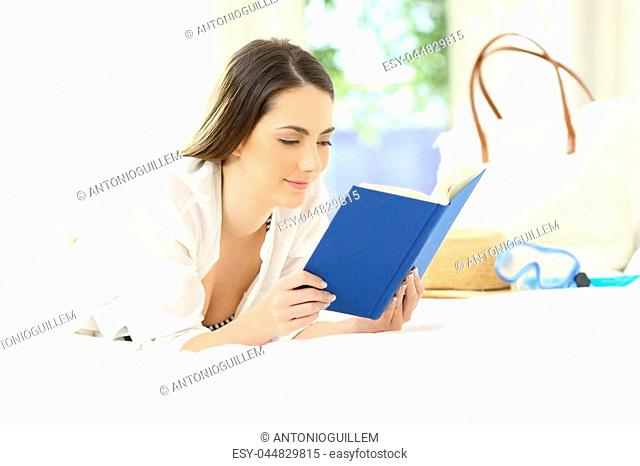 Relaxed woman reading a book in an hotel room on summer vacations on the beach
