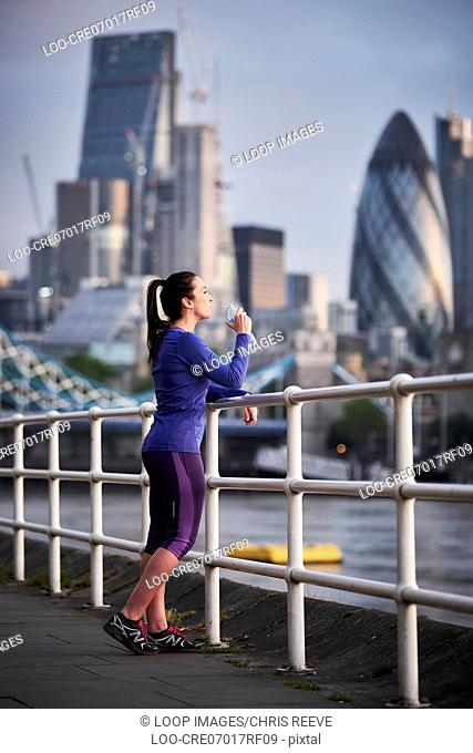 A woman resting after a run alongside the River Thames in London
