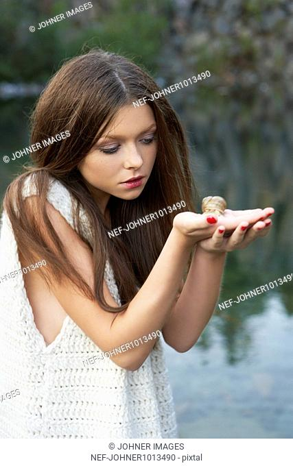 Woman holding snail on palm