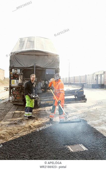 Manual workers spreading tarmac at road construction site