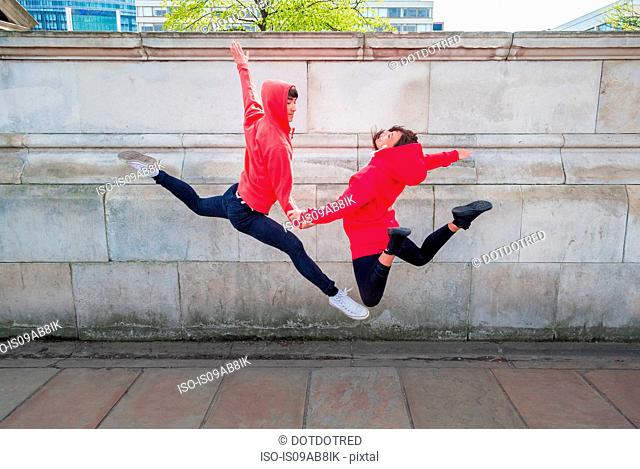 Young male and female dancer mid air in city