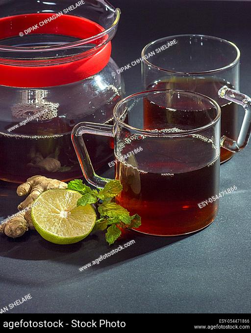 Cup of tea, mint and lemon on dark background