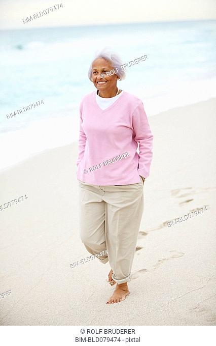 Senior African American woman walking on beach
