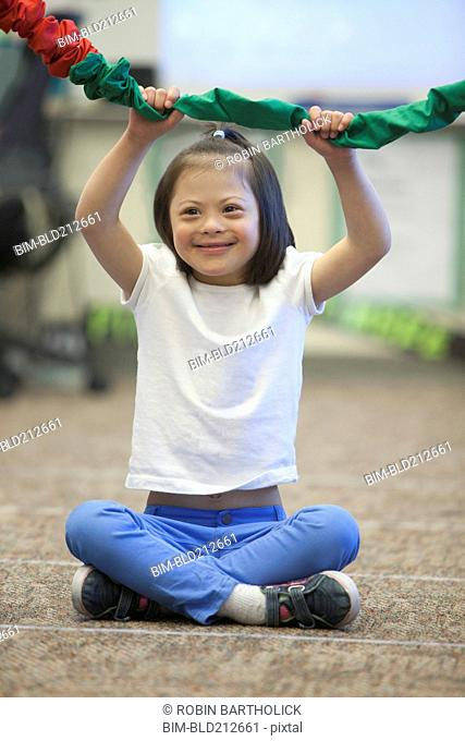 Mixed race Down syndrome girl playing with rope
