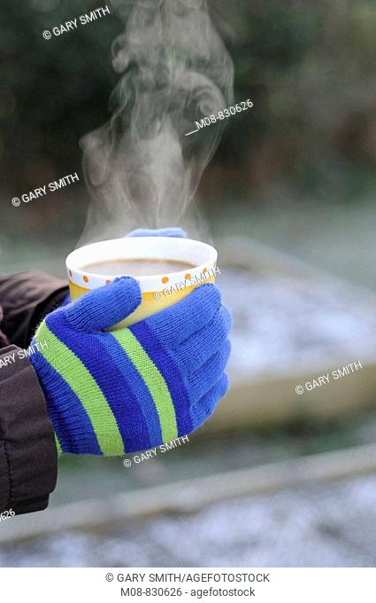 Lady gardeners hands in gloves holding steaming cup of coffee in garden, January