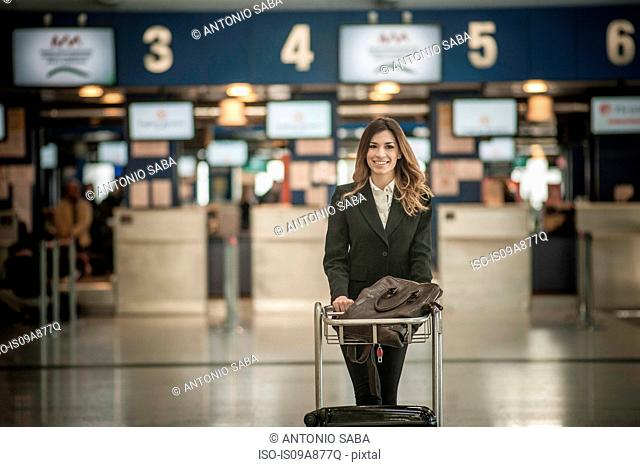 Young woman with luggage trolley in airport