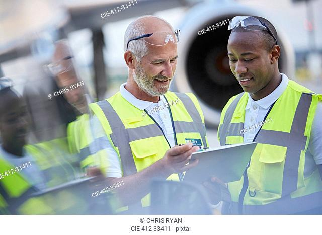 Air traffic control ground crew workers talking using digital tablet on airport tarmac