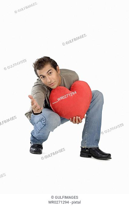 Young man holding heart-shaped cushion, portrait