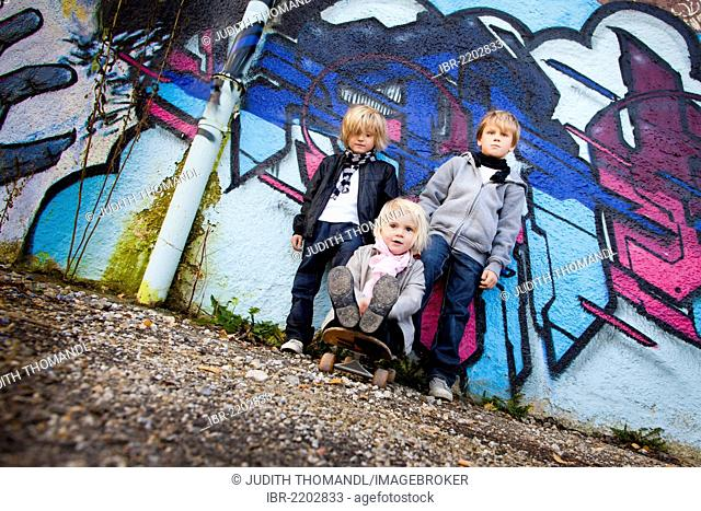 Siblings, 2, 5 and 7 years, in front of a wall with graffiti