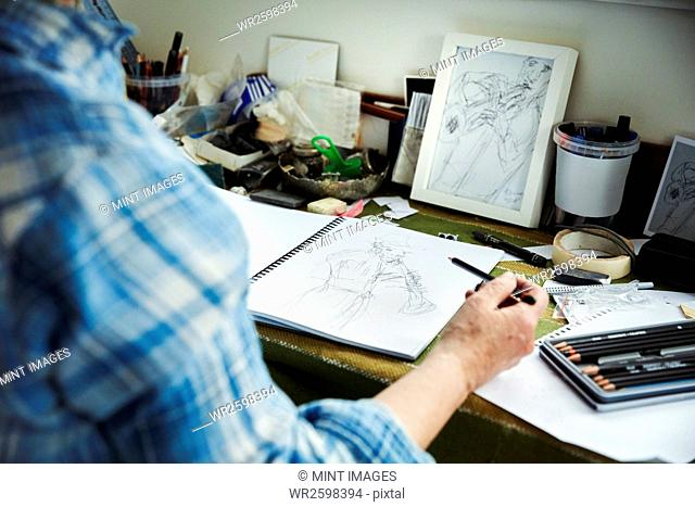 An artist working, holding a pencil over a sketch in progress in an open sketchbook