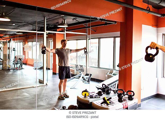 Reflection of mid adult man looking at himself in gym mirror training with kettle bells