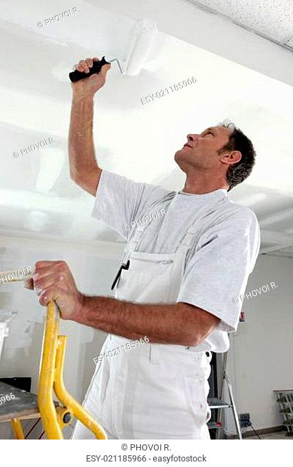 Man painting a ceiling white