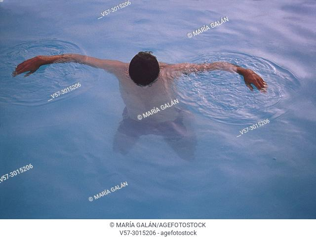 Man floating on the water in a swimming pool