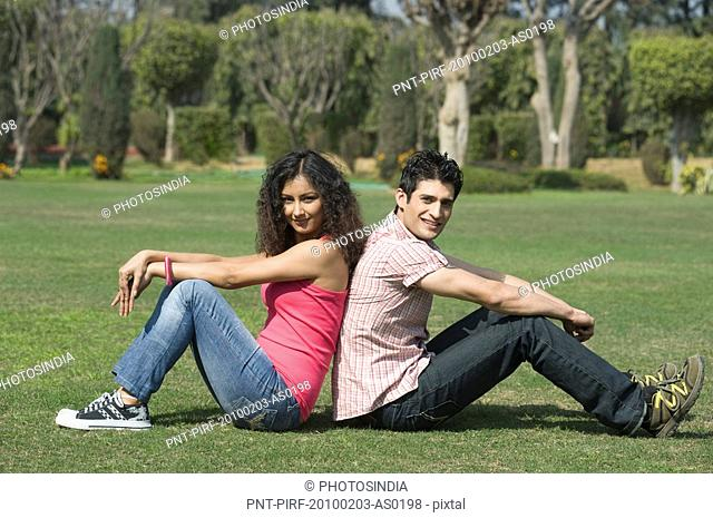 Couple sitting back to back in a park