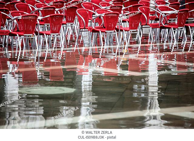 Cafe chairs in flooded St Mark's Square, Venice, Italy