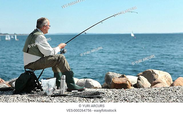 Happy retired man fishing on some rocks with all his gear next to him, turning to smile at the camera