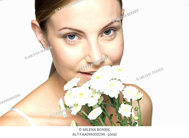 Young woman smelling bouquet of daisies