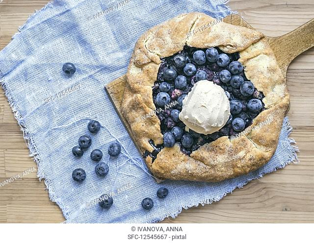 Rustic blueberry pie with ice-cream on a wooden board and white tissue